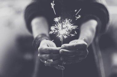 Monochrome photo of woman hands holding fire light sparkler