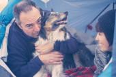 Liebes- und Freundschaftskonzept mit Mann und Frau und ziemlich entzückendem Collie-Hund, der vom Besitzer umarmt wird - blaue Farben und Freizeitaktivitäten für Menschen, die Tiere lieben