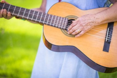 Close up of old aged senior female hands playing a guitar outdoor with green bokeh in background