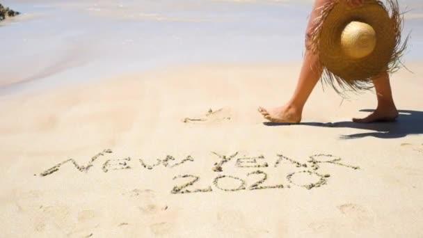 új év kártya sablon a nő gazdaság Szalmakalapot és gyalogos a homokos tengerparton