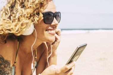 Pretty girl with curly hair and short jeans enjoying at beach while listening music