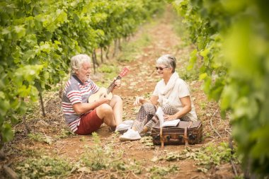 couple of older travelers sitting down in vineyard with luggage and playing on ukulele