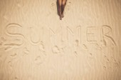 Photo Aerial vertical view of nude  woman legs and summer word written on the sand