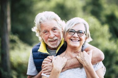 couple of cheerful happy senior people smiling and hugging in relationship