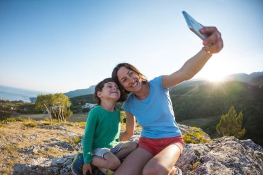 A woman with a boy on top of a mountain. Mother and son make selfie on the background of a beautiful landscape. Traveling with a child. Overnight in the countryside.