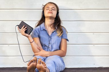 Teen barefoot girl wearing headphones enjoying music from a smartphone and singing outdoors in warm ummer evening