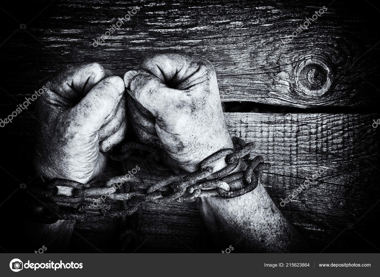Black and white image of the powerful dirty male hands clenched into fists chained with rusty chain on wooden background with copy space photo by