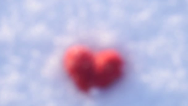 Kamera yaklaşımlar ve kar üzerinde yalan kırmızı yün kalp için odaklanır