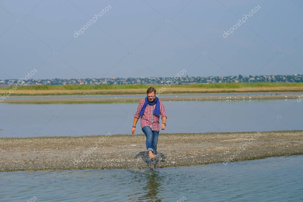 a man in blue jeans and a red shirt walking the river