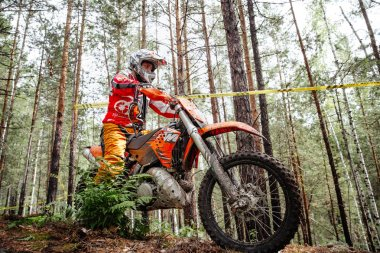 Kyshtym, Russia - July 21, 2019: athlete racer motocross enduro riding uphill in forest trail during Ural Cup in Enduro