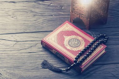 Holy book and beads on table