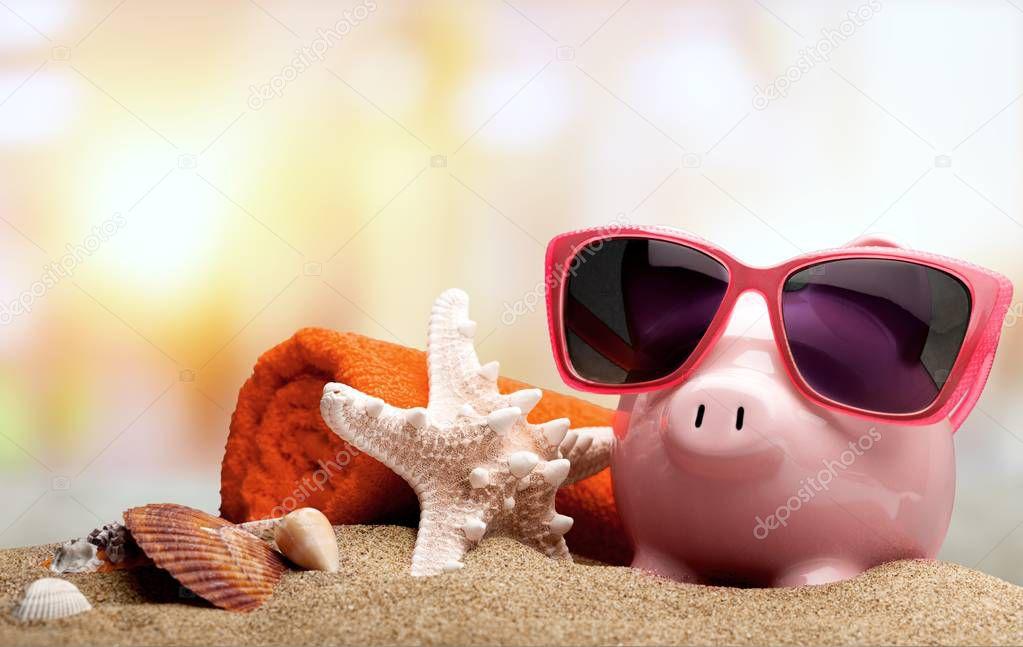 piggybank with sunglasses, shells, starfish and towel on sandy beach, travel concept