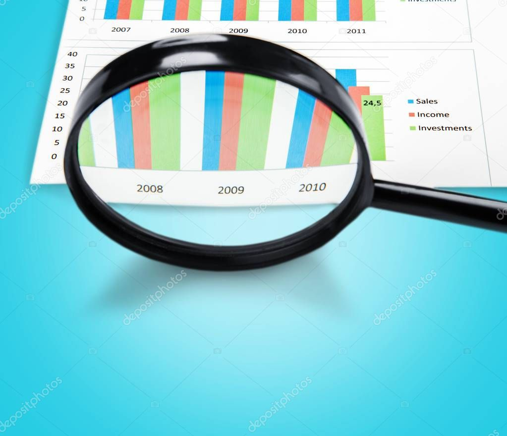 Magnifying Glass and Calculator on Business Graphs and