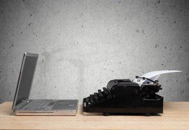 Old fashioned typewriter with a modern laptop
