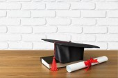 Graduation hat, book and diploma on wooden table