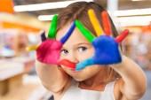 malá holčička ukazující malované ruce