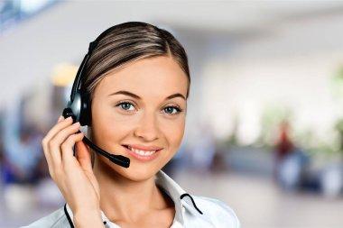 Customer service representative, young smiling woman talking through headset