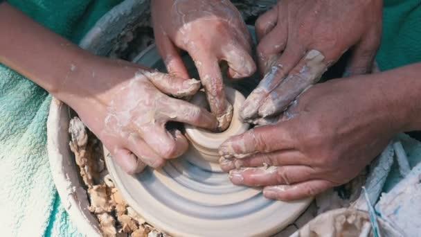 Draufsicht auf Töpferhände, die mit Ton auf einer Töpferscheibe arbeiten. Zeitlupe