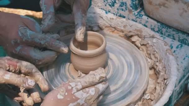 Hände des Töpfermeisters und Vase aus Ton auf der Töpferscheibe