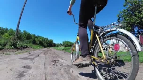 Mladá žena jízda historických kol po venkovské silnici ve vesnici. Zpomalený pohyb.