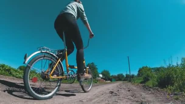 Mladá žena jízda historických kol po venkovské silnici ve vesnici