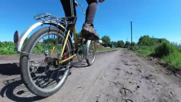 Fiatal nő lovaglás Vintage kerékpár egy vidéki úton a község