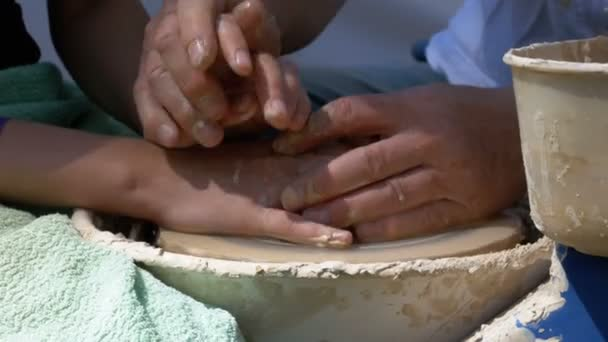 Hände des Töpfermeisters und Vase aus Ton auf der Töpferscheibe aus nächster Nähe.