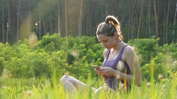 Happy Young Woman Sitting on Green Lawn and Uses Smartphone on Scenic Field at Sunset Background