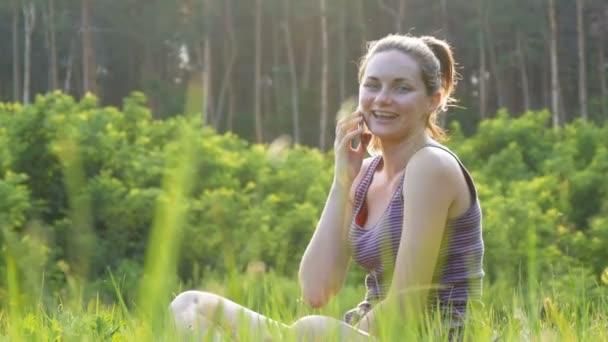 Glückliche junge Frau sitzt auf grünen Rasen und reden auf dem Handy oder Smartphone