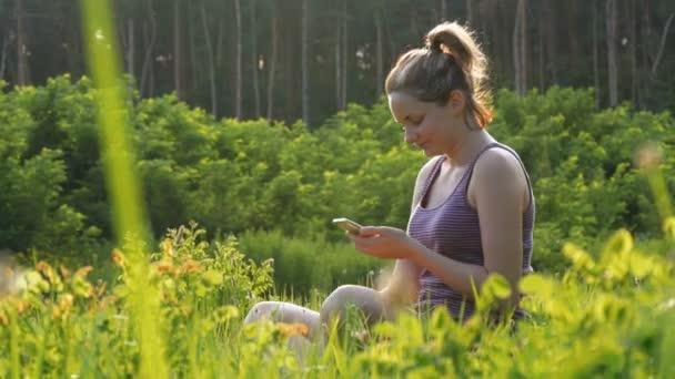 Glückliche junge Frau sitzt auf dem grünen Rasen und nutzt Smartphone auf malerischen Feld bei Sonnenuntergang Hintergrund