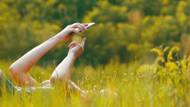 glückliche junge Frau, die auf grünem Rasen liegt, nutzt Smartphone auf malerischem Feld bei Sonnenuntergang