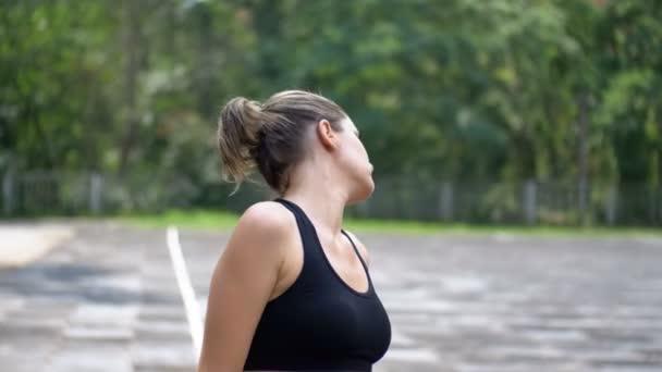 Mladá žena sportovní v oblečení Sport dělá krk na sportovní hřiště v parku