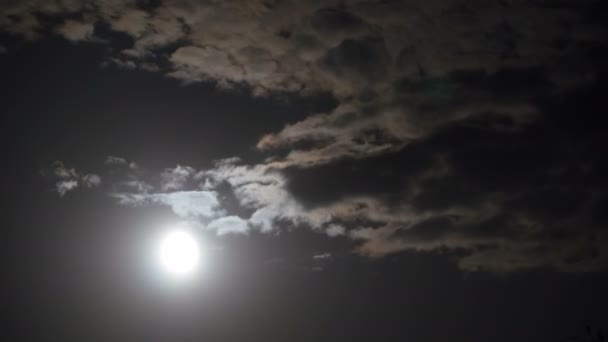 Full Moon Moves in the Night Sky through Dark Clouds. Time lapse