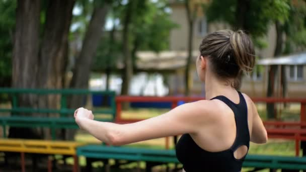 Mladý sportovní sportovní dívka provádí ohřátí rukou na sportovní hřiště v parku