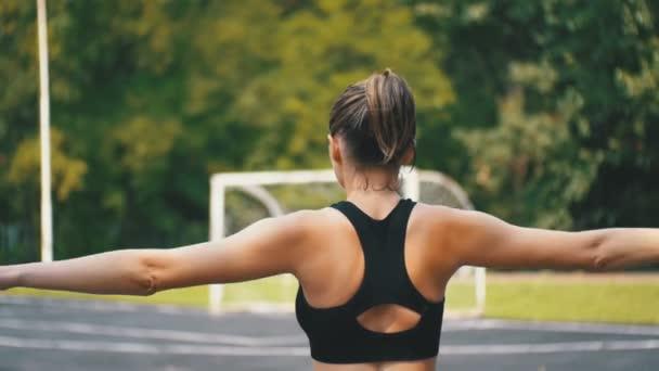 Zadní pohled na mladé sportovce ženy v Sport oblečení snoubenců ve Fitness na sportovní hřiště v parku.
