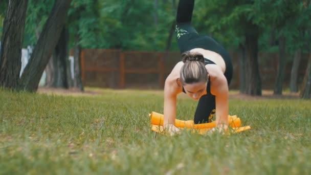Junge Sportler Frau im Sport-Outfit engagiert praktizieren Yoga liegen auf einem Teppich in einem Park auf einem grünen Rasen