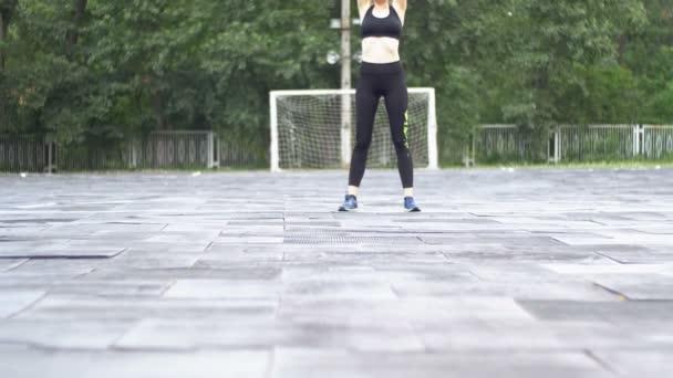 Mladý sportovec žena v sportovní ústroj zabývají Fitness na sportovní hřiště v parku.