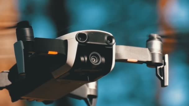 Drone with a camera hovers in the air. Quadcopter flies above the ground in the forest
