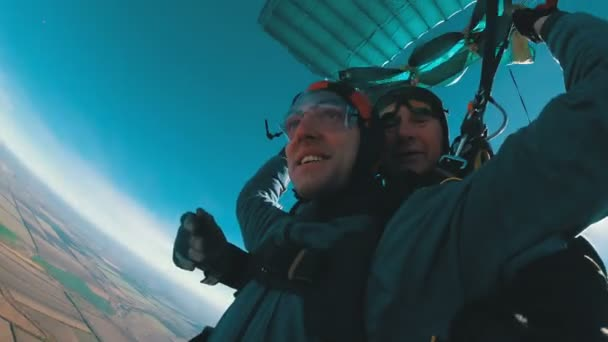 Skydivers flying in tandem under the open parachute