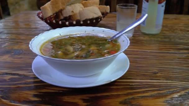 Gruzínská Houbová polévka v talíř na dřevěný stůl v restauraci. Apetitnye gruzínské kuchyně.