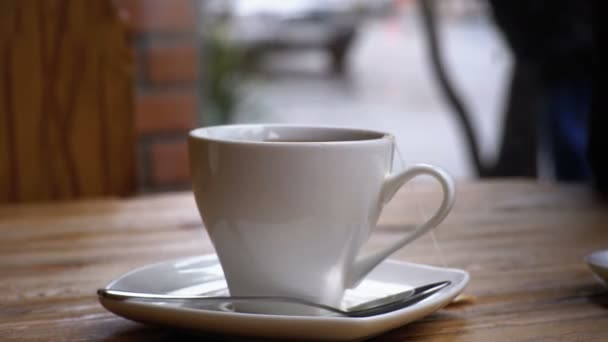 White Cup of Hot Tea on the Table in a Cafe on the Background of the Street Window