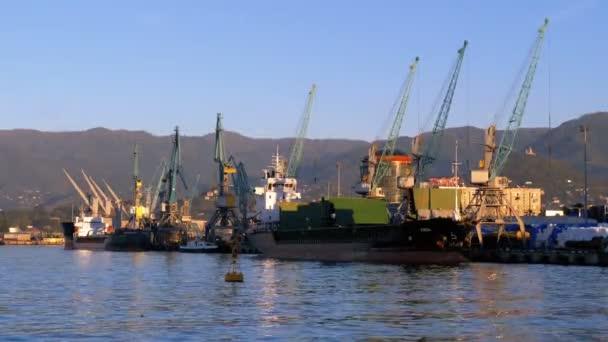 Námořní přístav Batumi s jeřáby, čluny a lodě na moři, na pozadí pohoří
