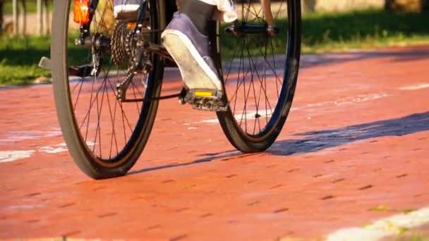 Muž na koni tři kolový elektrický skútr na cyklostezce v parku. Zpomalený pohyb