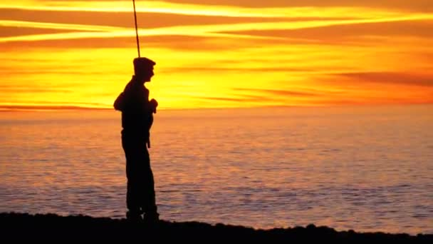 Sziluettjét, a halász, napnyugtakor a tenger fölött egy horgászbot