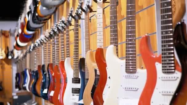 Sok elektromos gitár lógott egy zenebolt. Hangszer bolt