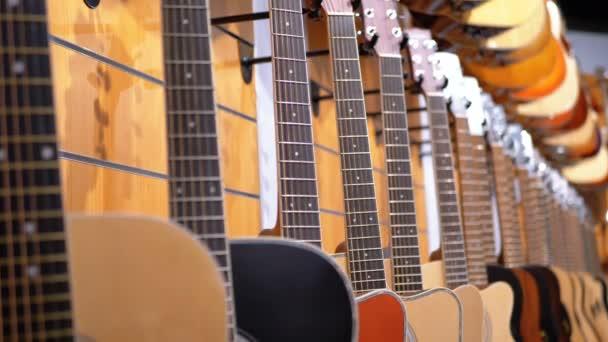 Sok akusztikus gitár lógott egy zenebolt. Hangszer bolt.