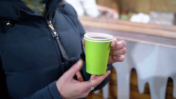 Frau trinkt Glühwein aus Plastikbecher, wenn sie im Winter auf der Straße steht