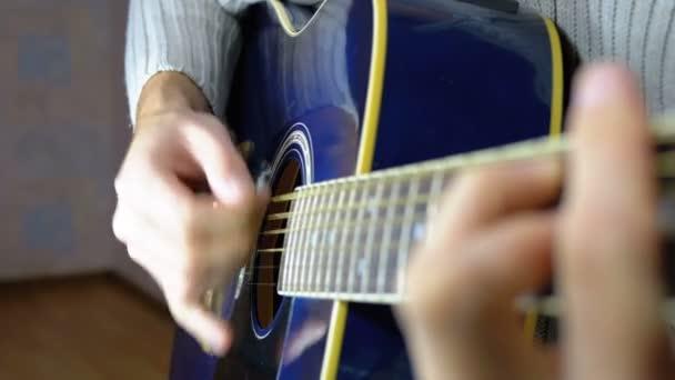 Ember játszik akusztikus gitár. Lassú mozgás