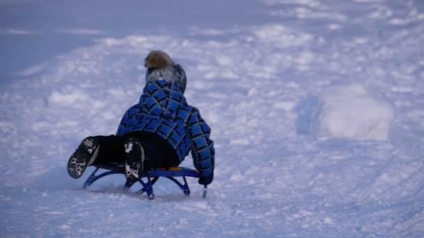 Kinder rodeln einen verschneiten Hügel hinunter. Zeitlupe