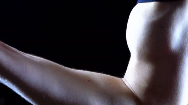 aufgepumpter Bizeps auf der Hand eines jungen Mannes auf schwarzem Hintergrund